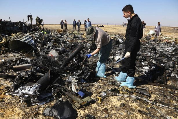 Russian investigators walks near wreckage a day after a passenger jet bound for St. Petersburg