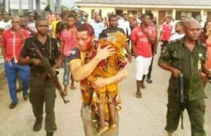 The suspect carrying his son's corpse in the presence of police and residents