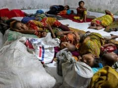 AFP / STR Bangladeshi families evacuated from their coastal villages sleep in a storm shelter as Cyclone Mora approaches