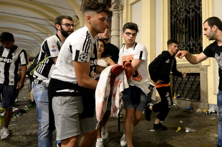 AFP / Massimo PINCA Juventus supporters carry an injured woman in Piazza San Carlo in Turin after a stampede in the fanzone where fans were watching the Champions League Final between Juventus and Real Madrid on a giant screen, on June 3, 2017