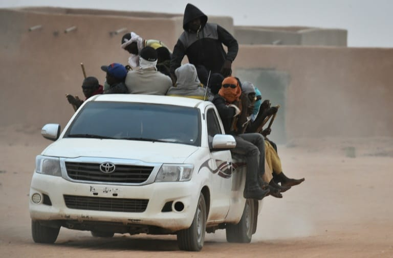 AFP/File / ISSOUF SANOGO A vehicle carrying migrants travels through Agadez, Niger, en route to Libya in June 2015