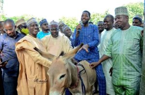Gandujes aide with the beneficiary of the donkey 719x470 1 300x196 - Kano: Governor Ganduje's Aide Shares Donkey To Empower Youths