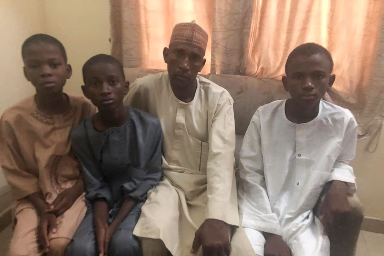 Abubakar Lawal is flanked by sons Buhari (in white) and Anas, with a fellow student (far left) who was also among those abducted on Dec. 11.