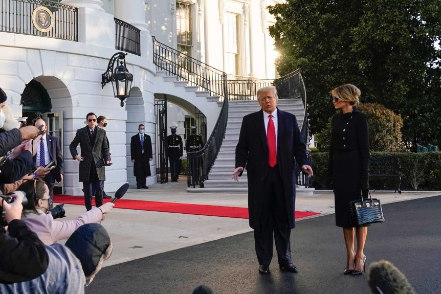 President Donald Trump and first lady Melania Trump stop to talk with the media as they leave the White House.(AP: Alex Brandon)