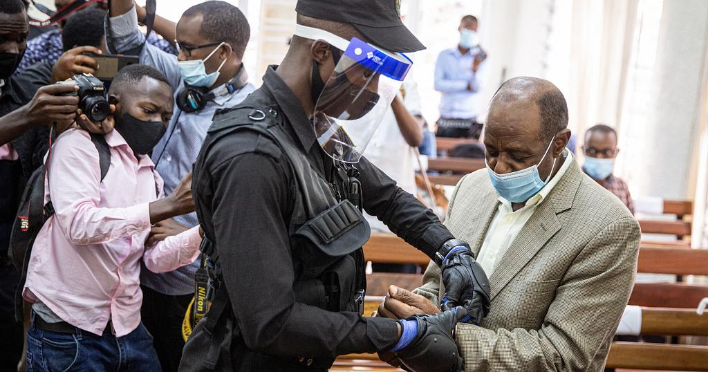 """In this file photo taken on September 14, 2020 """"Hotel Rwanda"""" hero Paul Rusesabagina (R) is handcuffed by a police officer after his pre-trial court session in Rwanda"""